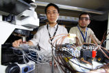 Han-Sheng Chuang and Ahmed Amin in lab monitoring performance of miniature chip